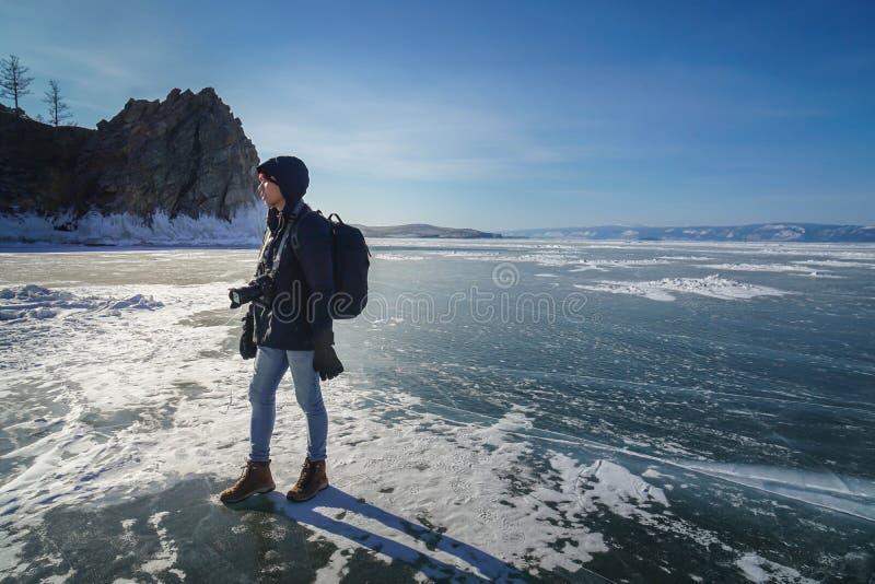 Mężczyzna w czarnej zimy kurtki solo podróży w zamarzniętym jeziornym Baikal z kamerą zdjęcie stock