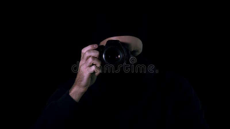 Mężczyzna w czerni maskowych robi fotografiach kamerą, tajna informacja, żąda okup obrazy royalty free