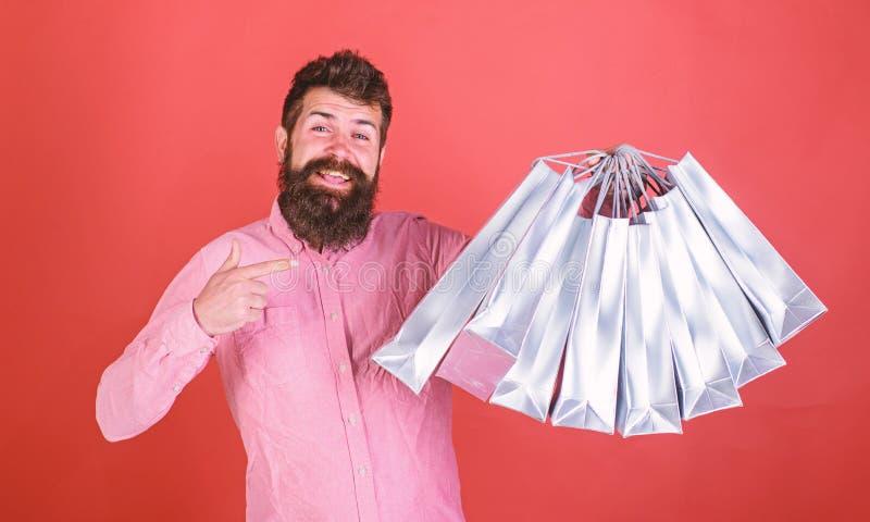 Mężczyzna wskazuje przy torba na zakupy z brodą i wąsy, czerwony tło Modniś na szczęśliwej twarzy jest robić zakupy uzależniam si zdjęcia stock