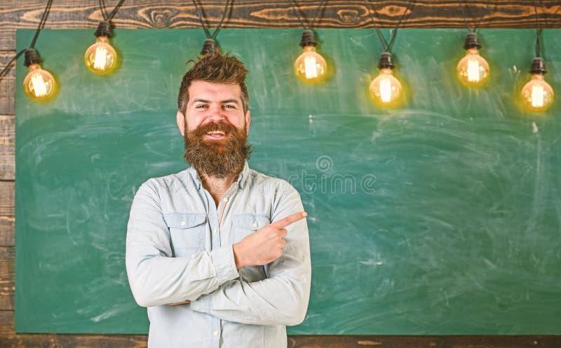 Mężczyzna z brodą i wąsy na szczęśliwym uśmiechniętym twarz stojaku przed chalkboard Brodaty modniś w koszula, chalkboard dalej obraz royalty free