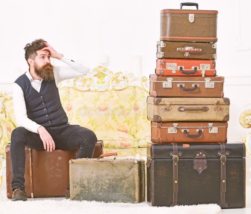 Mężczyzna z brodą i wąsy pakował bagaż, biały wewnętrzny tło Macho elegancki na zmęczonej twarzy siedzi, wyczerpywał przy, obrazy stock