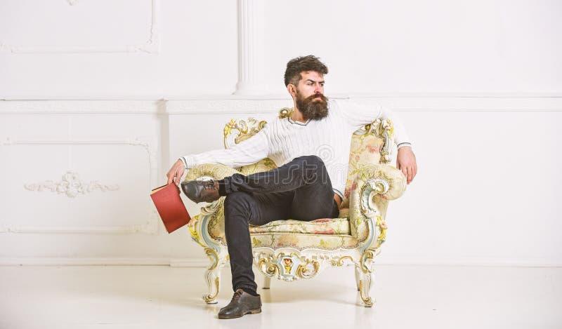 Mężczyzna z brodą i wąsy siedzi na karle, chwyty rezerwuje, bielu ścienny tło Odbicia na literatury pojęciu facet obraz stock