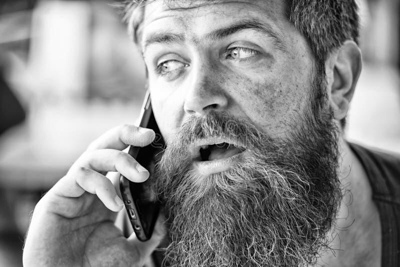 Mężczyzna z brody i wąsy telefonu komórkowego rozmowy defocused tłem Brodaty mężczyzny chwyta telefon komórkowy modniś obrazy stock