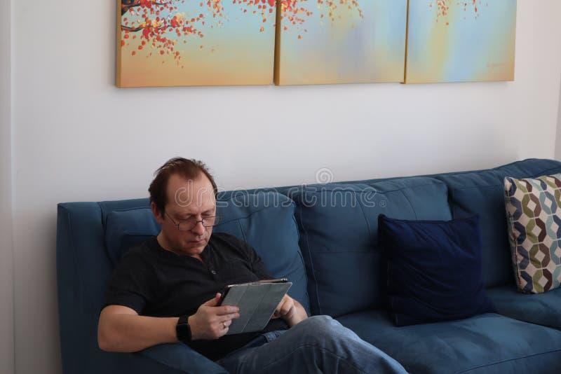 Mężczyzna z szkłami pracuje na pastylce obsługuje relaksować w izbowym obsiadaniu na leżance Zainteresowany atrakcyjny mężczyzny  fotografia stock