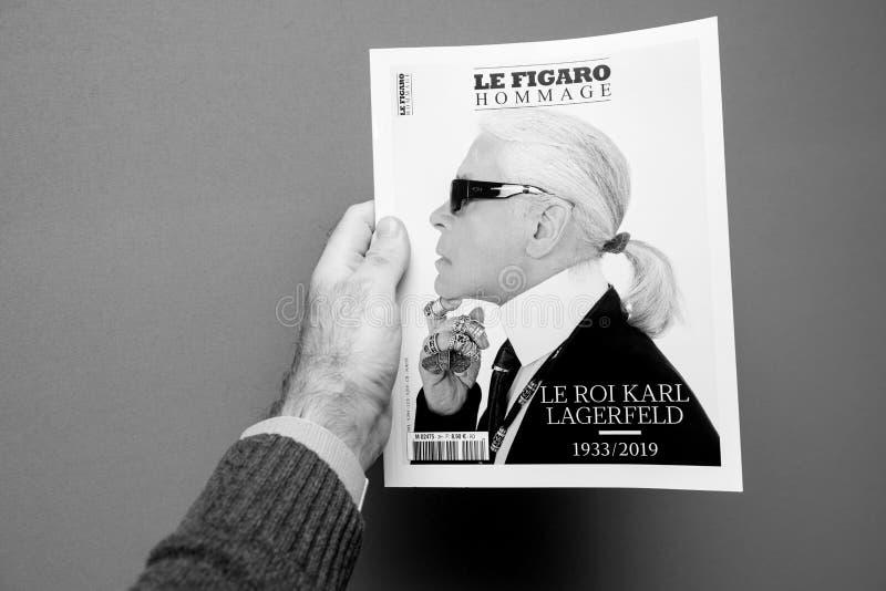 Mężczyzny mienia magazyny uwypukla okładkową Karl Lagerfeld śmierć obraz stock