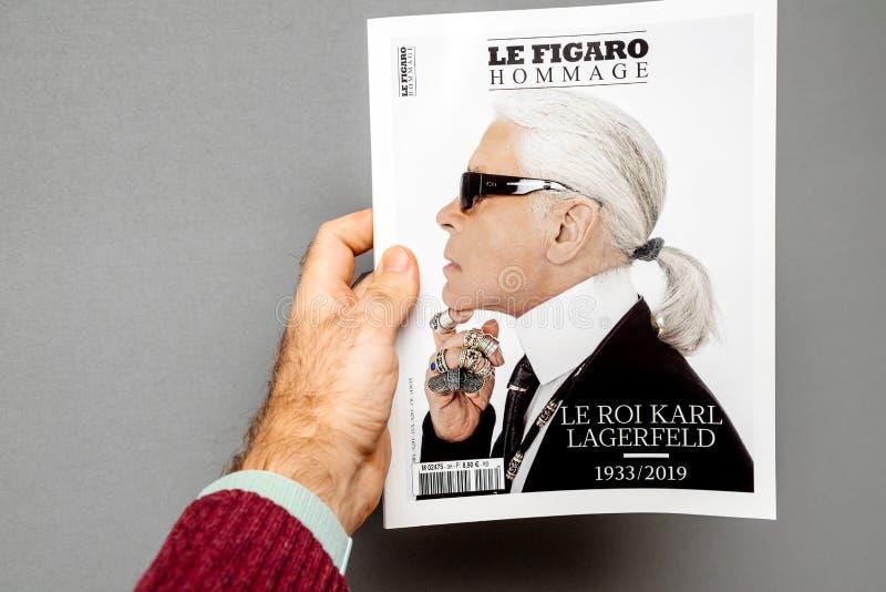 Mężczyzny mienia magazyny uwypukla okładkową Karl Lagerfeld śmierć fotografia stock