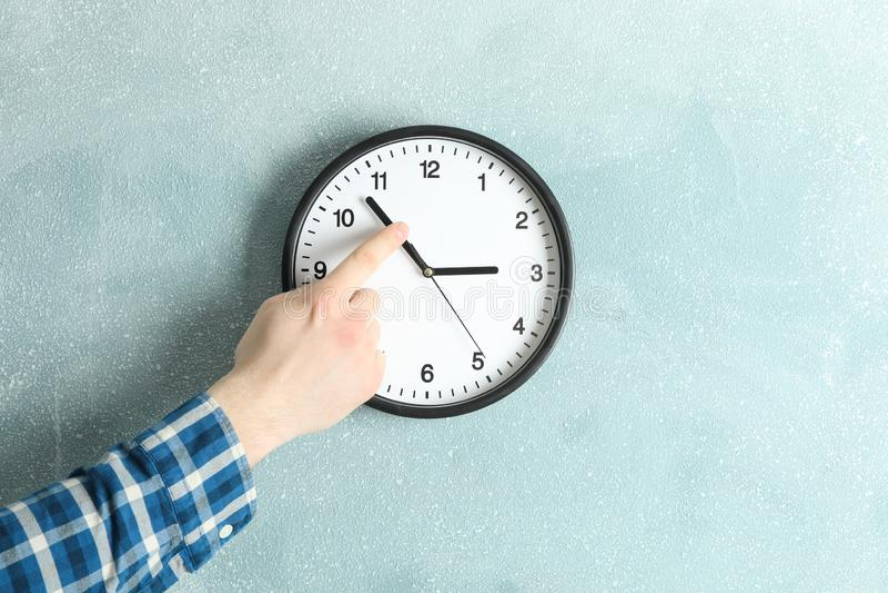 Mężczyzny odmieniania czas na pięknym ściennym zegarze zdjęcia stock