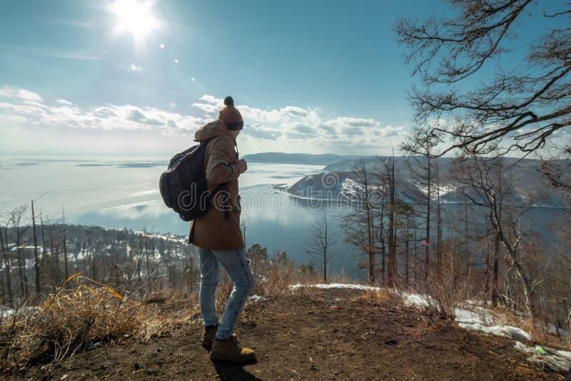 Mężczyzny podróżnika turystyczni stojaki na górze i spojrzenia przy pięknym widokiem jeziorny Baikal Styczeń 33c krajobrazu Rosji obraz stock