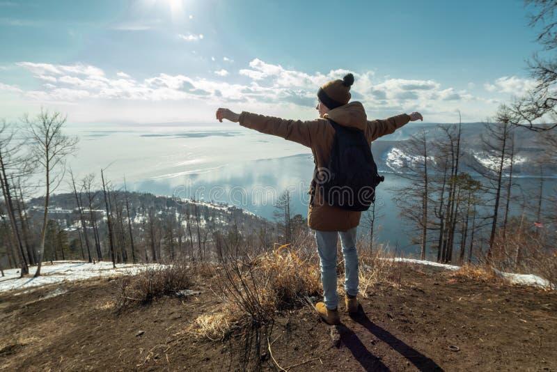 Mężczyzny podróżnika turystyczni stojaki na górze i spojrzenia przy pięknym widokiem jeziorny Baikal Styczeń 33c krajobrazu Rosji obrazy stock