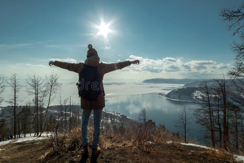 Mężczyzny podróżnika turystyczni stojaki na górze i spojrzenia przy pięknym widokiem jeziorny Baikal Styczeń 33c krajobrazu Rosji obraz royalty free