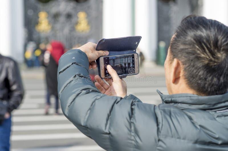 Mężczyzny turysta Azjatyckie pojawienie fotografie na pałac kwadracie St Petersburg, Rosja, Wrzesień 2018 widok od zdjęcie stock