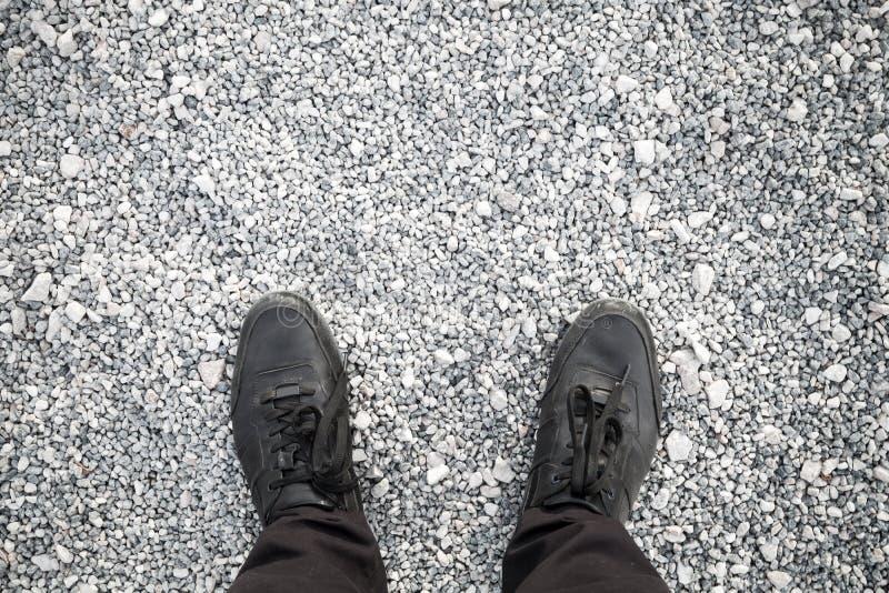 Męscy cieki w czarnych butach na otoczaku fotografia royalty free