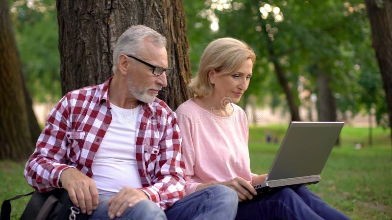 Męscy i żeńscy emeryci wybiera hotel dla wakacje na laptopie odpoczywa w parku obrazy stock