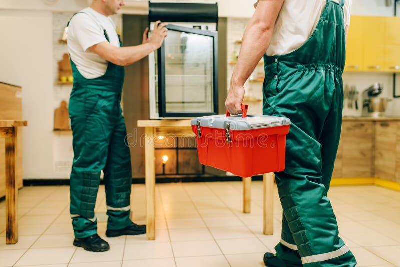 Męscy pracownicy w mundur naprawy chłodziarce obraz stock