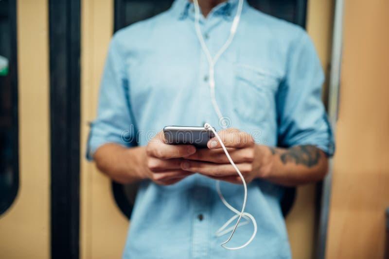 Męska osoba używa telefon w wagonie metru, nałóg fotografia stock