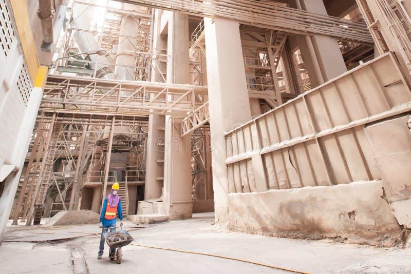Męski azjatykci laborer jest ubranym zbawczą ochronną przekładnię z ściekiem wśrodku wheelbarrow przy cementową fabryką fotografia stock