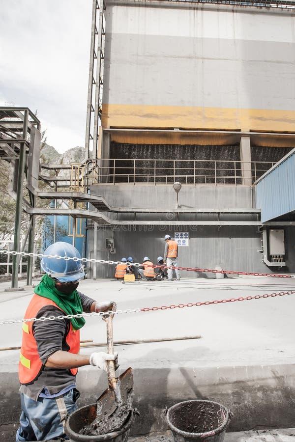 Męski azjatykci laborer z łopaty cleanout ściekiem w kanale ściekowym przy cementową fabryką Ciężkiej Pracy Pojęcie obraz stock