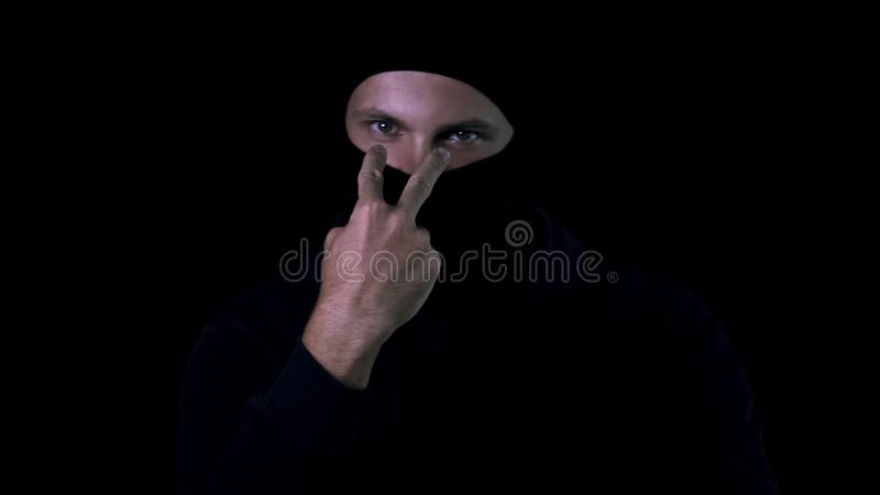 Męski bandycki czarny balaclava pokazuje oglądający ciebie szyldowego, osobisty bezpieczeństwo, niebezpieczeństwo obraz stock