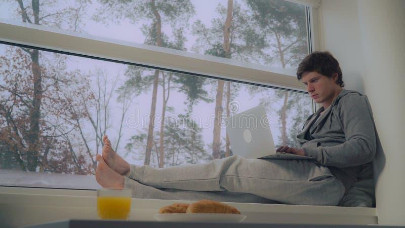 Męski działanie z komputerem osobistym w mieszkaniu zdjęcie stock