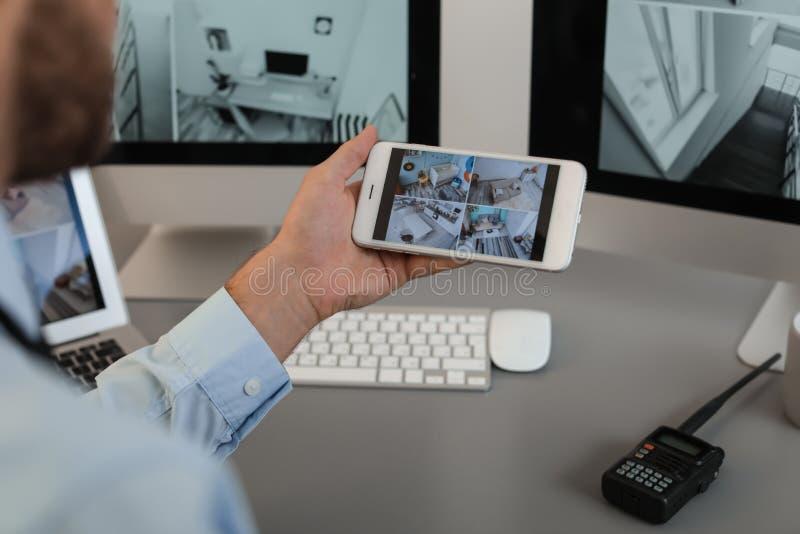 Męskie pracownika ochronego monitorowanie domu kamery używać smartphone indoors zdjęcia royalty free