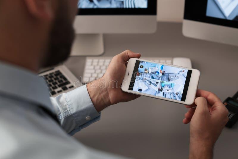 Męskie pracownika ochronego monitorowanie domu kamery używać smartphone indoors obrazy stock