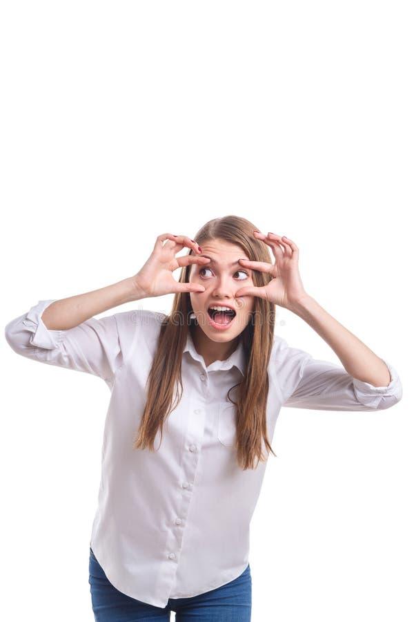Mädchen öffnet weit ihre Augen mit ihren Händen auf einem Weiß lokalisierten Hintergrund stockfoto