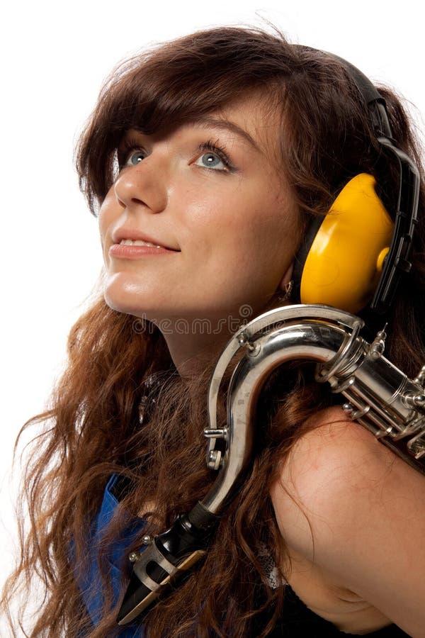 Mädchen in Arbeitsgesamten mit Saxophon stockfotografie