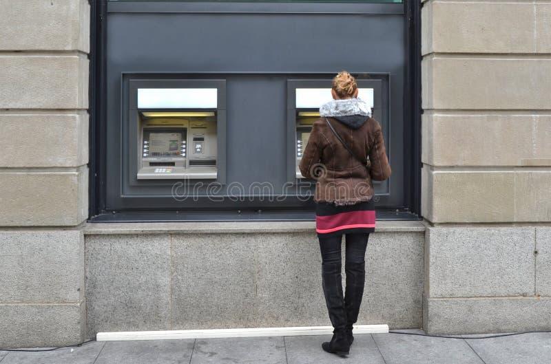 Mädchen an ATM stockfotos