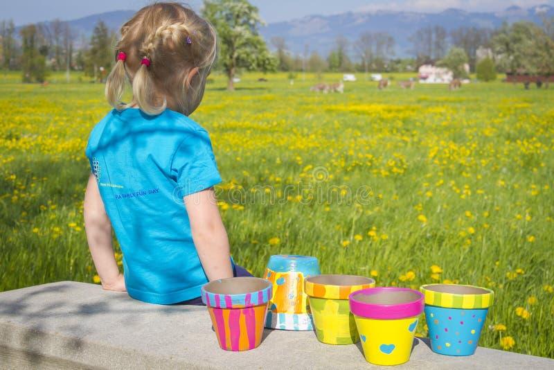 Mädchen auf blühendem Feld mit bunten gemalten Gartentöpfen lizenzfreie stockbilder