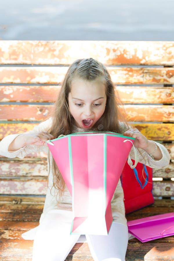 Mädchen auf dem überraschten Gesicht, das Einkaufstaschen oder Geschenke, Bank auf Hintergrund auspackt Kindermädchen mit dem lan lizenzfreie stockbilder