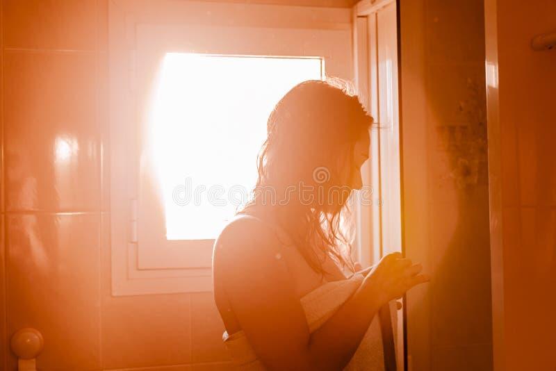 Mädchen auf dem Badezimmer in einem Badtuch bereit, eine Dusche zu erhalten Sonnenunterganglicht, das am Fenster kommt zuhause stockfotografie