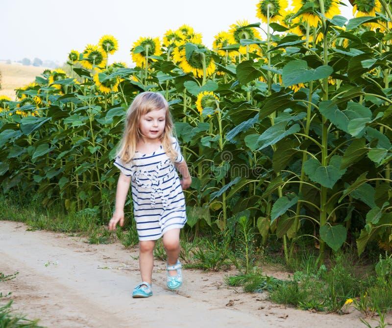 Mädchen auf dem Feld von Sonnenblumen lizenzfreie stockfotos