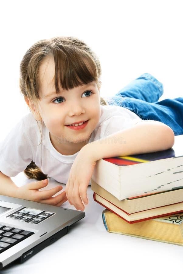 Mädchen auf dem Fußboden mit Büchern und einem Laptop stockfotografie