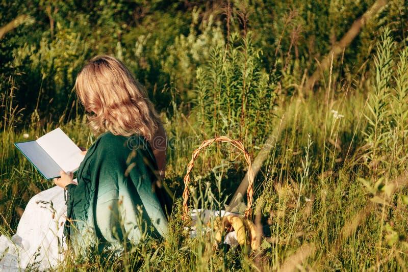 Mädchen auf dem Gebiet ein Buch lesend Das M?dchen, das auf einem Gras, ein Buch lesend sitzt stockfotografie
