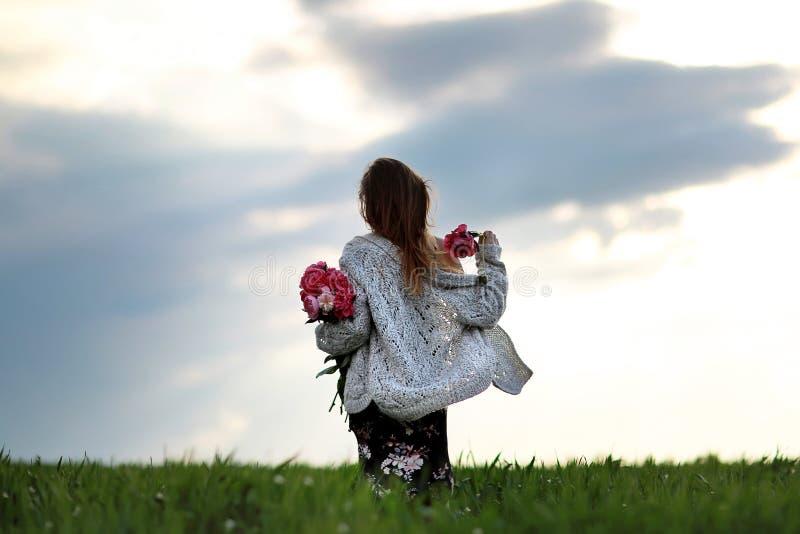 Mädchen auf dem Gebiet von Blumen Ein Mädchen mit Pfingstrosenwegen auf dem Gebiet stockfotos