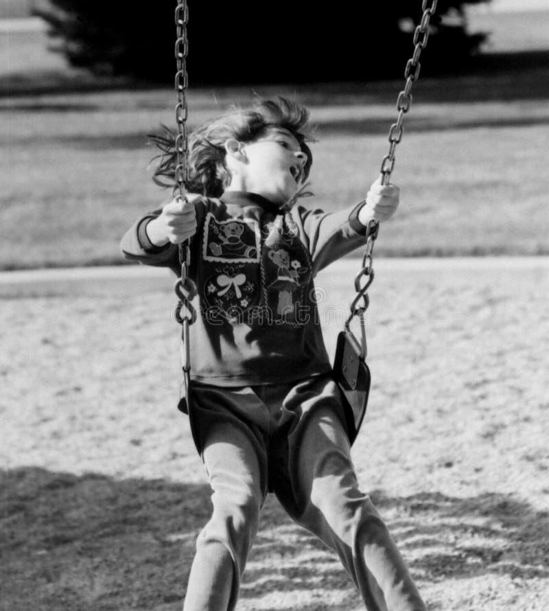 Mädchen auf dem Schwingen, das Spaß hat lizenzfreies stockbild