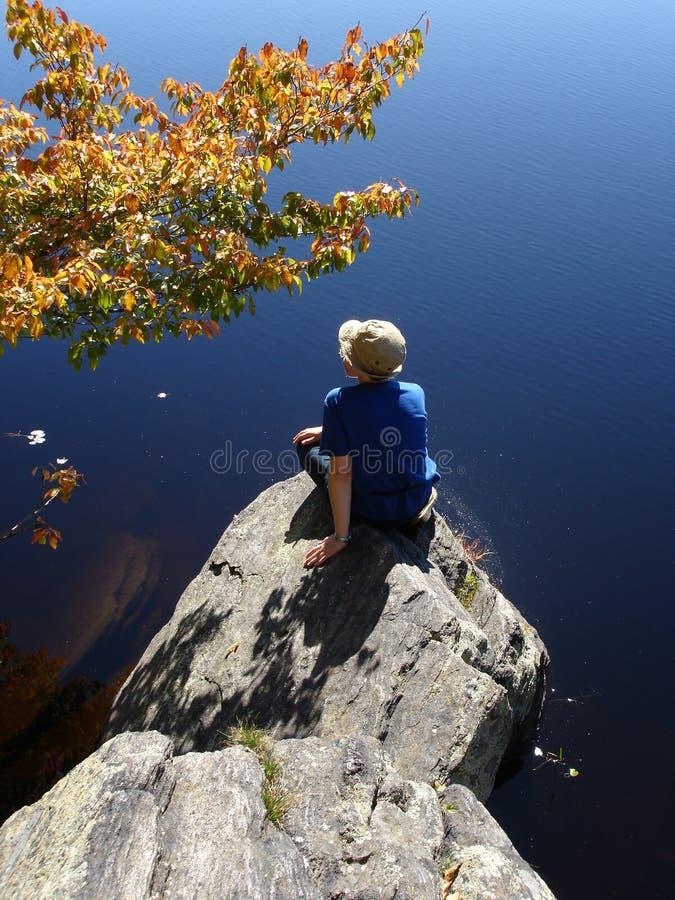 Mädchen auf dem Stein an Land stockfoto