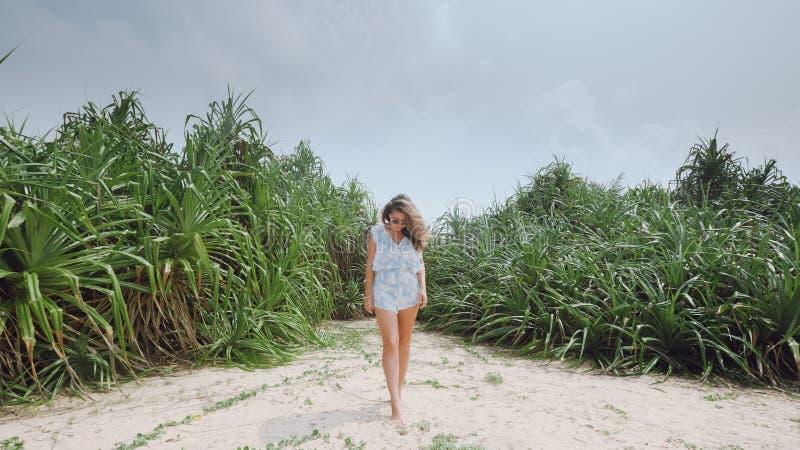 Mädchen auf dem Strand auf dem Hintergrund von tropischen Anlagen lizenzfreie stockbilder