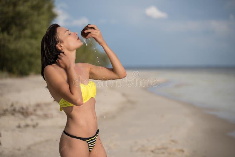 Mädchen auf dem Strand mit Kokosnuss stockbild