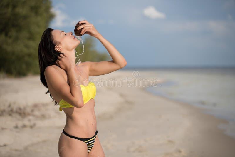 Mädchen auf dem Strand mit Kokosnuss lizenzfreie stockfotos