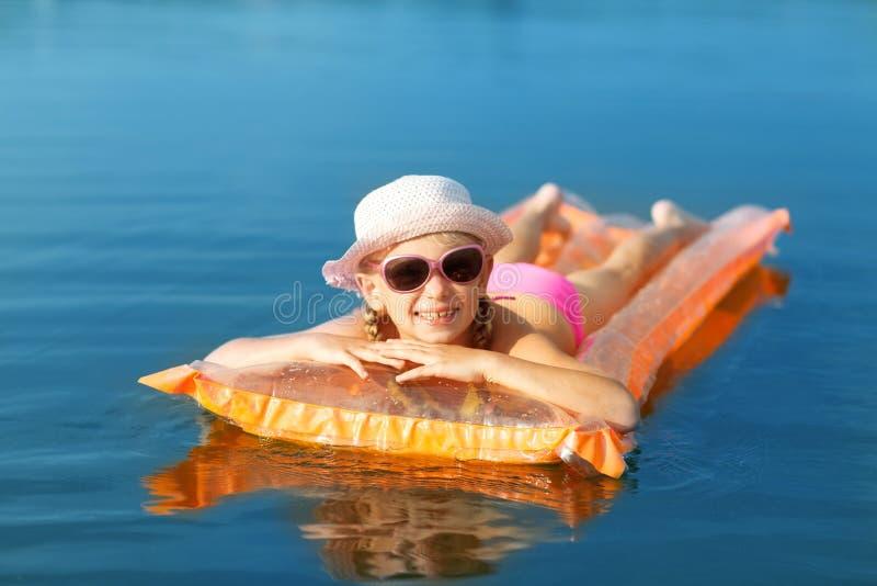 Mädchen auf der Schwimmenmatratze lizenzfreie stockbilder