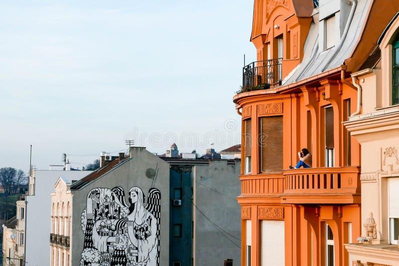 Mädchen auf einem Balkon Sonnenuntergang in Belgrad genießend stockbild