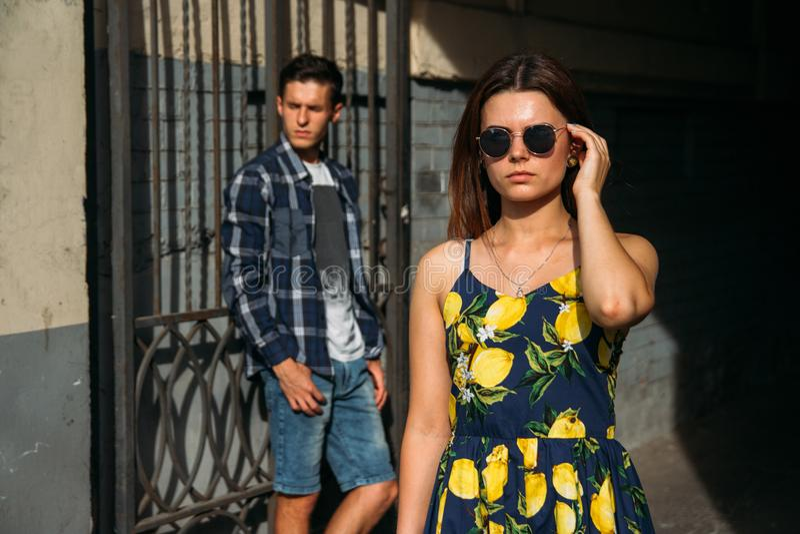 Mädchen auf einem dunklen Hintergrund in der Sonnenbrille, von hinten einen Kerl nahe einer Eisentür, Gitter Streit, gehen aus stockbild