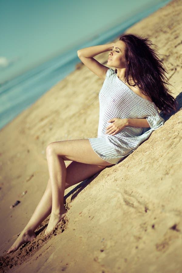 Mädchen auf einem Strand auf der Sonne auf einer Ozeanküste lizenzfreie stockfotografie
