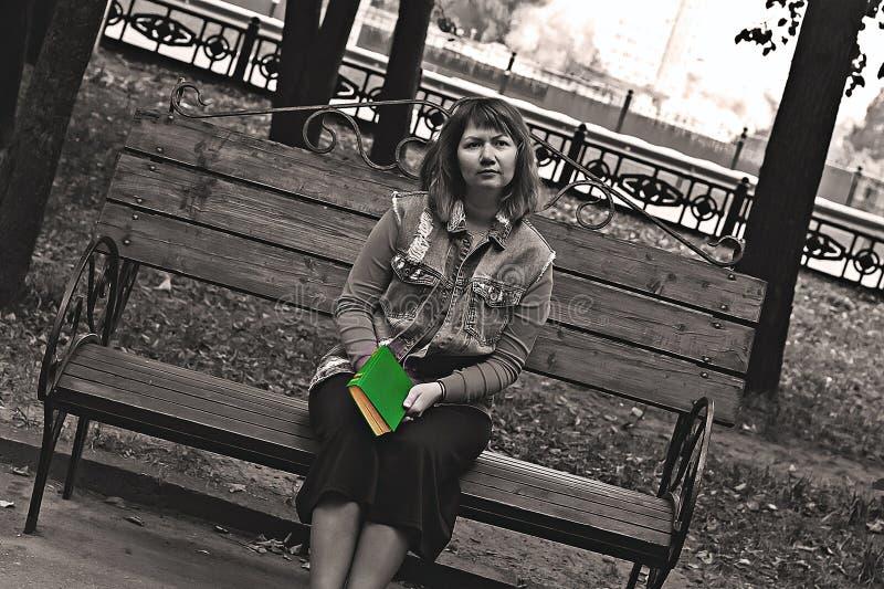 Mädchen auf einer Bank im Park mit einem Buch in ihren Händen, Schwarzweiss-Foto lizenzfreies stockbild