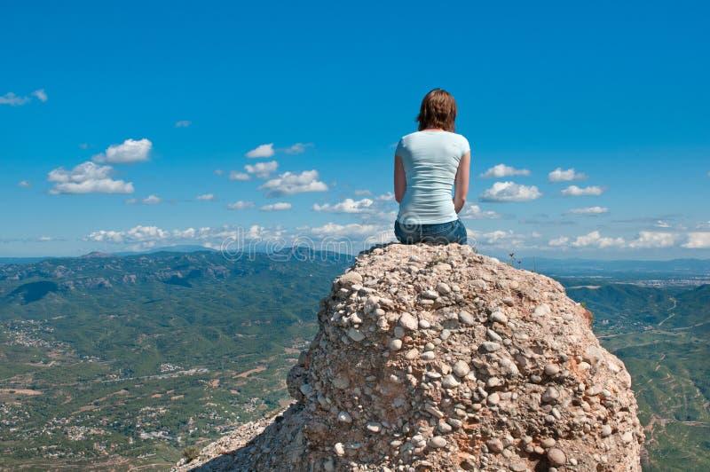 Mädchen auf einer Klippe, die Ansicht betrachtet stockfotografie