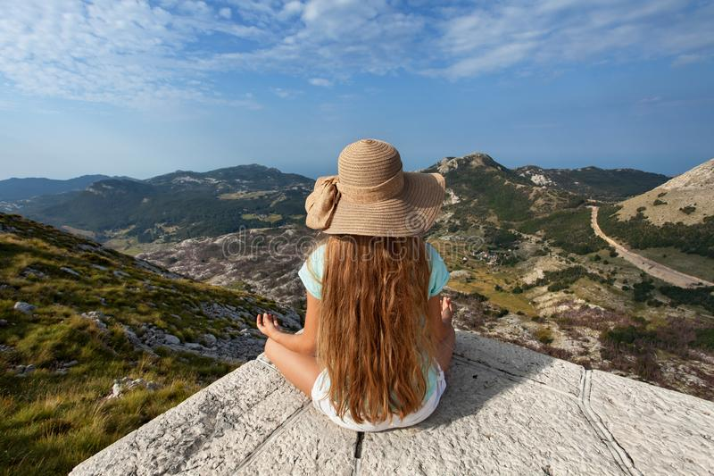 Mädchen auf Gebirgsspitzensitzen und die Ansicht bewundern stockfotos
