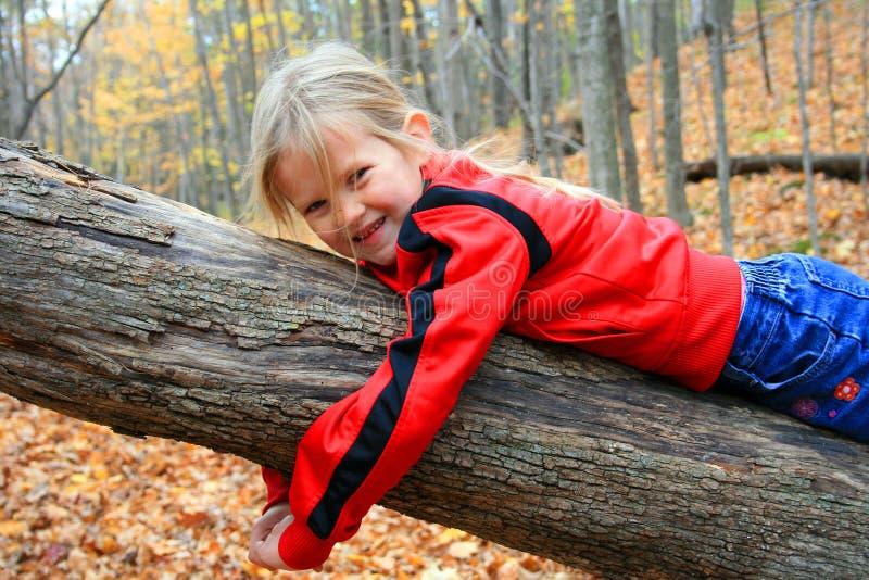 Mädchen auf gefallenem Baumkabel. stockfoto