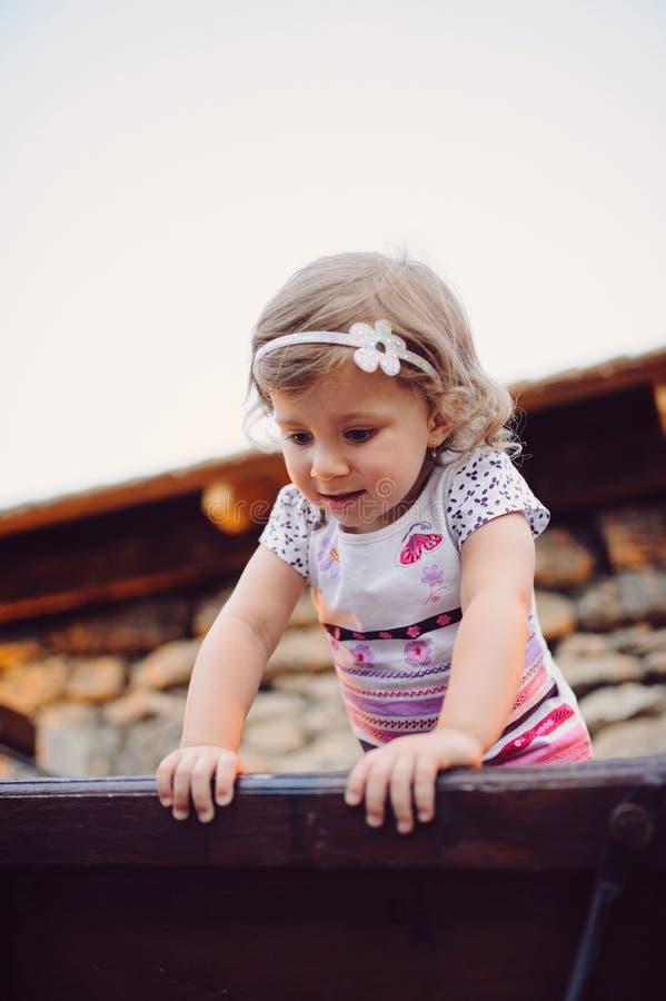 Mädchen auf hölzernem Portal lizenzfreies stockfoto