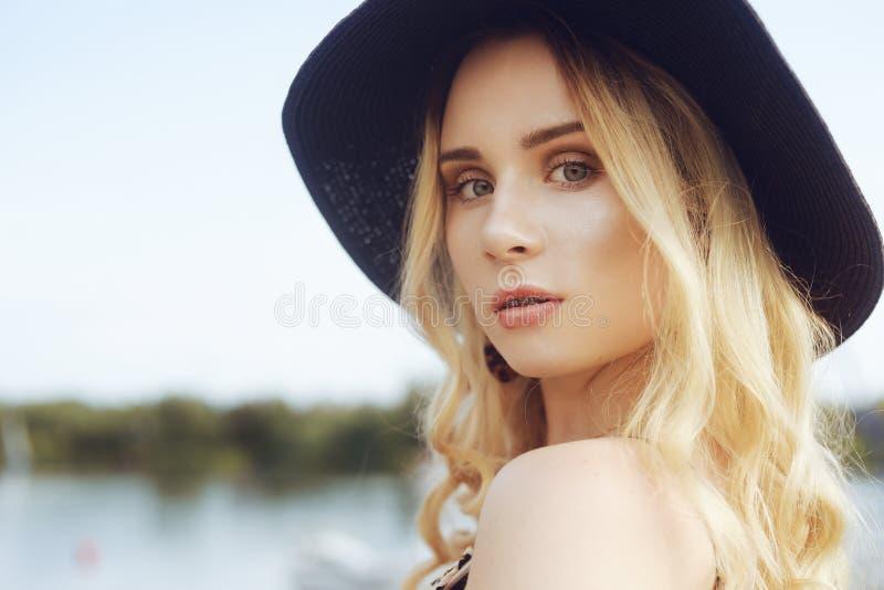 Mädchen auf Hintergrund von Yachten, Segelboote Lächeln, die Kamera betrachtend schöne Blondine sitzt auf dem Pier, in einem Klei lizenzfreie stockbilder